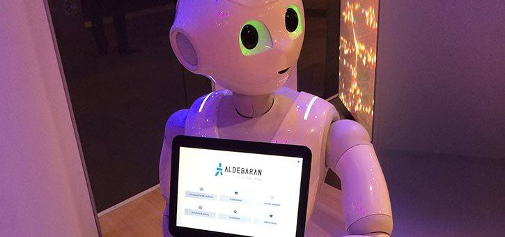 A robot with an iPad using chatbots for marketing.