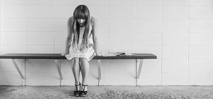 A young woman with Depression sitting alone.