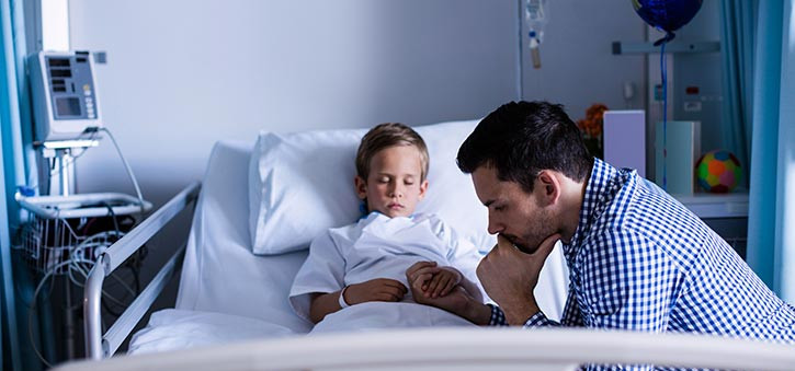 A father beside his son in a Hospital Bed.