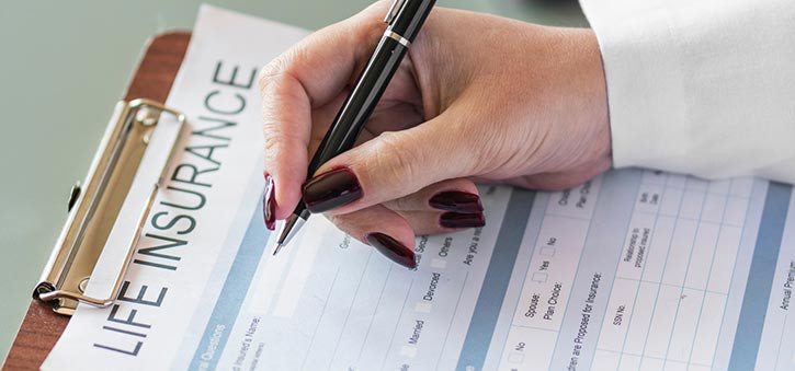 A woman filling out a Life Insurance form.