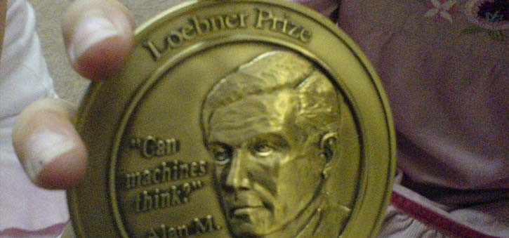 A closeup of someone holding the Loebner Prize Medal.