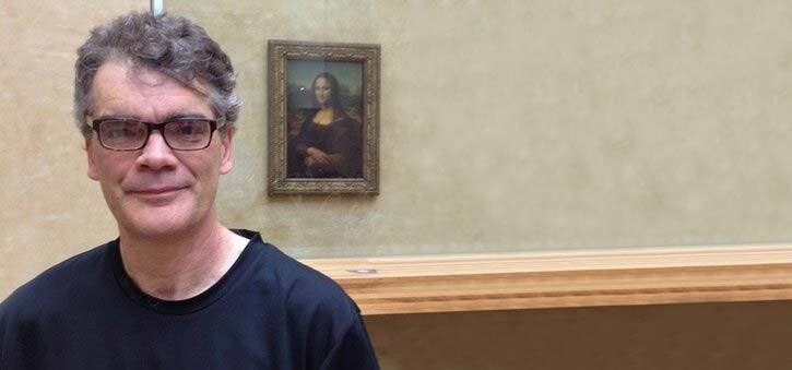 Dr. Richard Wallace standing in front of the Mona Lisa.